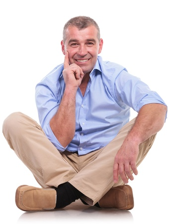 casual senior man sitting on the floor with his legs crossed and holding his hand at his chin, in a pensive way, while smiling for the camera. isolated on white background photo