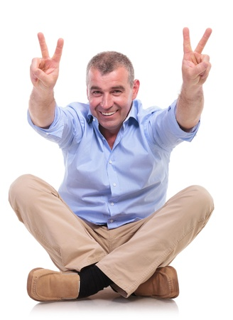 casual senior man sitting on the floor with his legs crossed and shows victory sign with both hands. isolated on white background photo