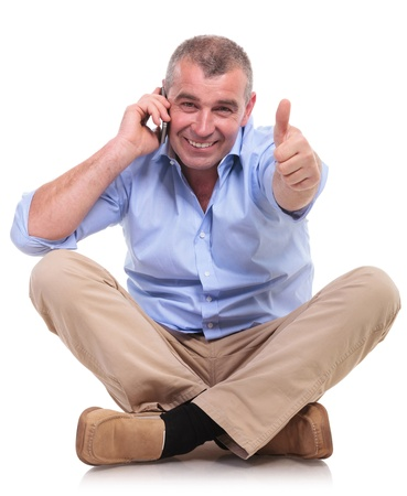 casual senior man sitting on the floor with his legs crossed and talking on the phone while showing thumbs up gesture and a smile for the camera. isolated on white background photo