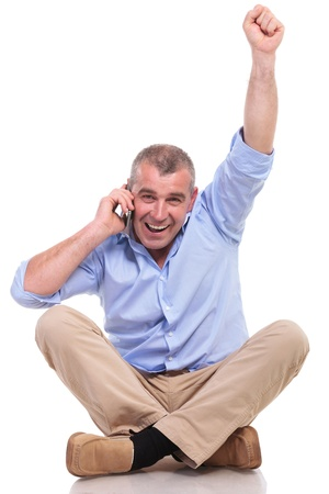 casual senior man sitting on the floor with his legs crossed and cheering while speaking on the phone and looking at the camera. isolated on white background photo
