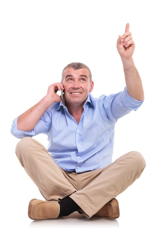 legs folded: casual senior man sitting on the floor with his legs crossed and talking on phone while pointing and looking upwards, above him. isolated on white background
