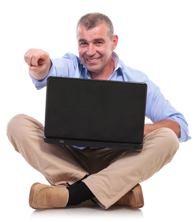 casual senior man sitting on the floor with his legs crossed and holds his laptop while pointing at the camera with a smile on his face. isolated on white background Stock Photo - 20054466