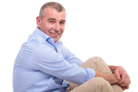 side view of a casual senior man sitting on the floor with his legs crossed and looking at the camera with a charismatic smile on his face. isolated on white background photo