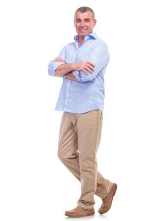 volle lengte foto van een toevallige senior man die met de armen over elkaar en kijken naar de camera. geïsoleerd op witte achtergrond