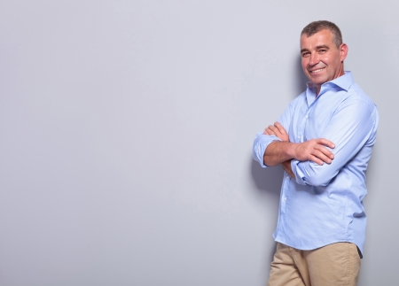 casual senior man standing with his hands crossed and smiling for the camera . on gray background Фото со стока