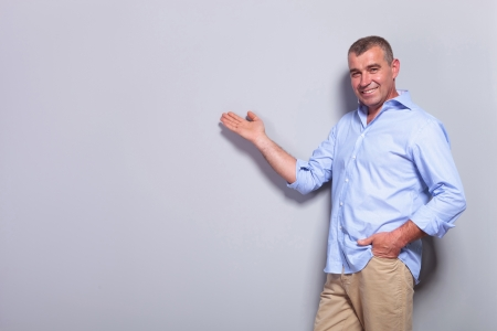 casual senior man presenting something with a hand in his pocket and a smile on his face. on gray background photo