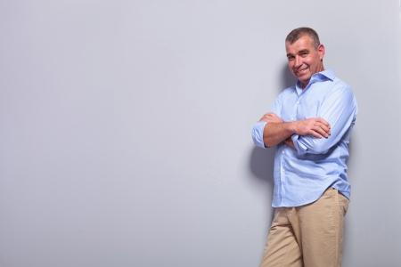 casual senior man standing with his hands crossed against a gray background and smiling at the camera photo