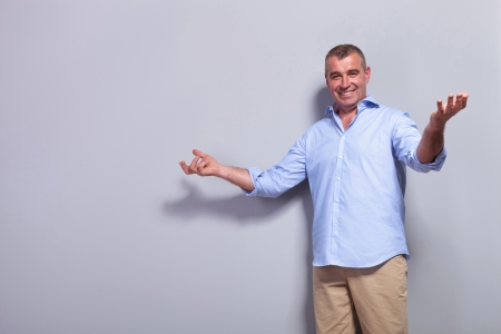 casual senior man welcoming you with a big smile. on gray background photo