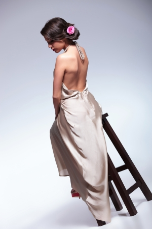 back view photo of a young beauty woman sitting on a high chair and looking down. on gray background photo