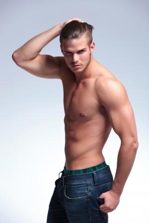 seins nus: vue de côté d'un jeune homme torse nu debout avec sa main dans ses cheveux et l'autre dans sa poche arrière tout en regardant la caméra. sur fond gris