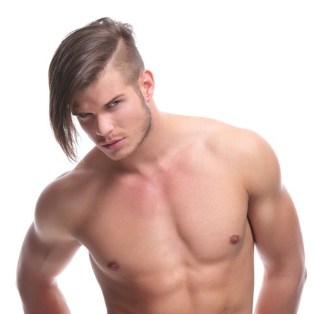 closeup portrait of a young fashion topless man looking at the camera while holding his hands in his back pockets. isolated on white background photo