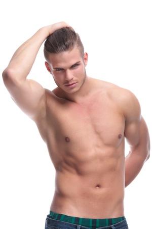 seins nus: jeune topless de la mode homme tenant une main dans son dos et tenant ses cheveux avec l'autre. isolé sur fond blanc Banque d'images