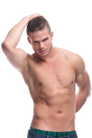 topless jeans: young fashion topless man holding a hand at his back and holding his hair with the other. isolated on white background