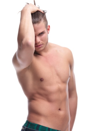 young fashion topless man adjusting his hair while holding a hand in his back pocket and looking into the camera. isolated on white background photo