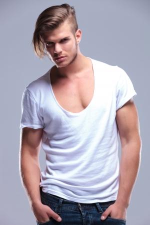 r boy: el hombre de moda joven posando con las manos en los bolsillos mientras mira a la cámara. sobre fondo gris