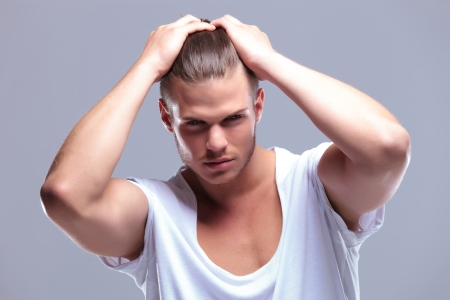 man with long hair: closeup of a young fashion man holding his hair with both hands while looking at the camera. on gray background Stock Photo