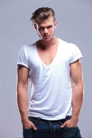 top model: jonge mode man die met zijn handen in zijn zakken, terwijl kijken naar de camera. op een grijze achtergrond