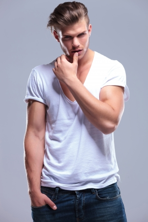 poses de modelos: el hombre de moda joven con la mano en el bolsillo y el pulgar sobre el labio inferior mientras mira a la cámara. sobre fondo gris