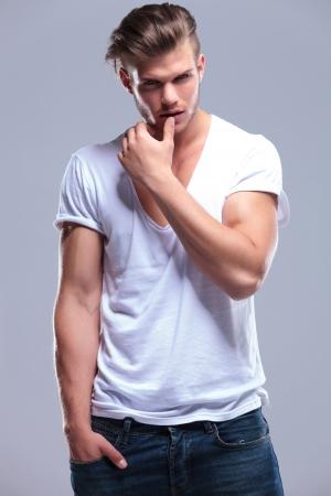 mann mit langen haaren: junge Mode Mann h�lt seine Hand in seine Tasche und seine Daumen an seiner Unterlippe, w�hrend in die Kamera schaut. auf grauem Hintergrund