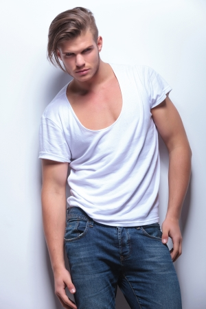 hair background: young fashion man posing in a low-cut shirt and looking at the camera. on light gray background