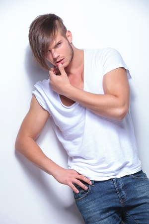 young fashion man holding a hand on his hip and the other at his mouth while looking at the camera. on light gray background