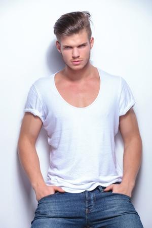poses de modelos: el hombre de moda joven con las manos en los bolsillos y mirando a la cámara. sobre fondo gris claro Foto de archivo