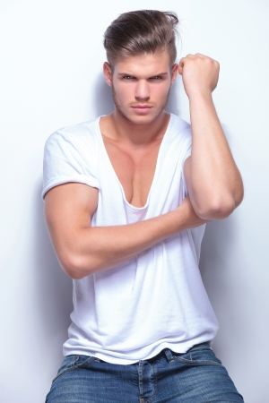 appealing attractive: young fashion man showing his biceps while looking at the camera. on light gray background