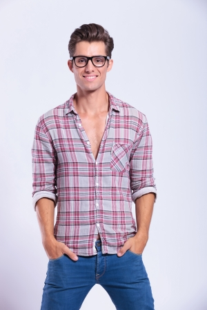 waistup: casual young man standing with his hands in his pockets and smiling at the camera. on gray background