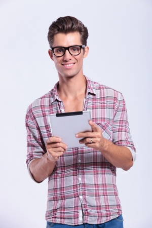 casual young man holding his talet with both hands and smiling at the camera. on gray background photo