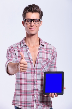casual young man presenting a tablet and showing thumb up. on gray background photo