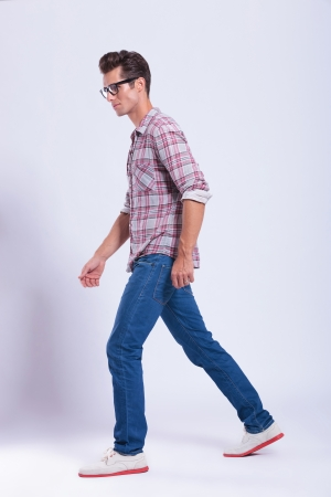 perpendicular: full length picture of a casual young man walking and looking away from the camera. on gray background