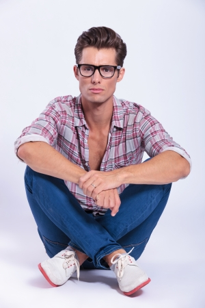 casual young man sitting on the floor with legs crossed and looking at the camera with a serious expression. on gray background photo