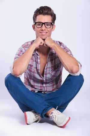 mani incrociate: casual giovane uomo seduto con le gambe incrociate e tenendo le mani al mento con un sorriso sul suo volto. su sfondo grigio