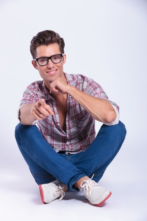 sitting on the ground: casual young man  sitting with his legs crossed and pointing at the camera while holding his hand at his chin and smiling. on gray background Stock Photo