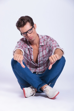 man legs: casual young man sitting with his legs crossed showing both thumbs down. on gray background Stock Photo