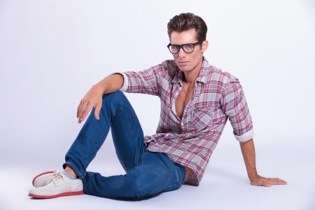 assis par terre: Casual jeune homme posant sur le sol et regardant la cam�ra. sur fond gris