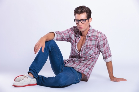 casual young man posing on the floor and looking at the camera. on gray background