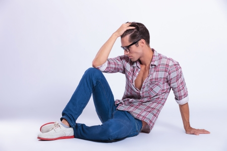 sitting on the ground: casual young man posing on the floor with his hand through his hair and looking down, away from the camera. on gray background