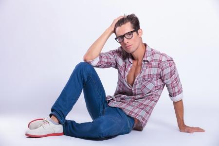 assis par terre: Occasionnel jeune homme pose sur le sol et posant avec sa main dans ses cheveux tout en regardant la cam�ra. sur fond gris