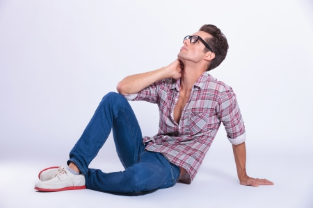 sitting on the ground: casual young man posing on the floor with his hand at his neck and looking up, away from the camera. on gray background