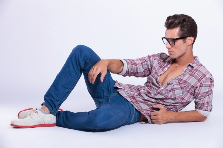 lying down on floor: casual young man posing on the floor while looking away from the camera. on gray background Stock Photo