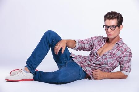 assis par terre: Casual jeune homme posant s�rieux tout en vous relaxant sur le plancher. sur fond gris Banque d'images