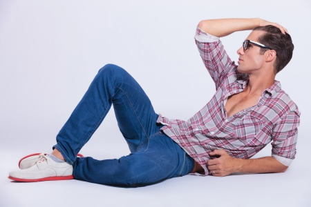 sitting on the ground: casual young man laying on the floor and putting his hand through his hair while looking away from the camera. on gray background Stock Photo
