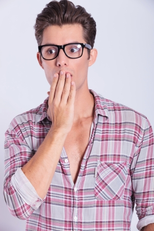 hand over: closeup portrait of a casual young man remaining speechless with his hand over his mouth and looking away from the camera. on gray background
