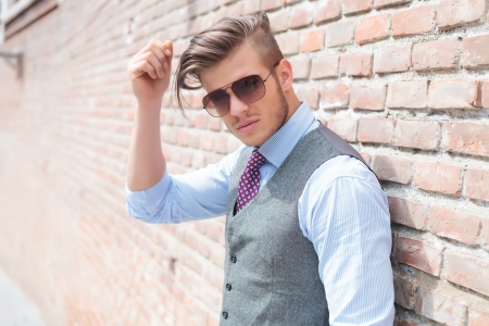 closeup of a casual young man standing against a brick wall and adjusting his hair while looking at the camera