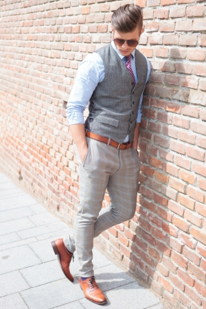 casual young man leaning on a brick wall and looking down while holding his hands in his pockets photo