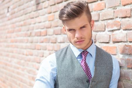 poses de modelos: Primer plano de un hombre joven ocasional que se inclina en una pared de ladrillo y mirando a la cámara