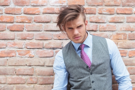 messed up: casual young man against a brick wall looking at the camera with his hair all messed up