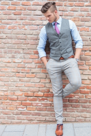 full length picture of a casual young man standing with his back at a wall and with his hands in his pockets while looking down photo