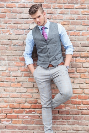 ties: casual young man with a leg on a brick wall and his hands in his pockets, looking into the camera Stock Photo
